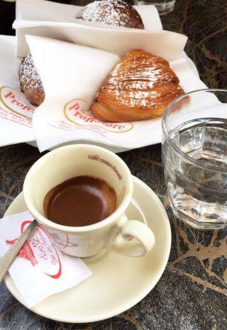Caffè napoletano servito con sfogliatella e tazzina bianca calda.